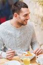Happy young man having dinner at restaurant Royalty Free Stock Photo