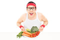 Happy young man holding a plate full of vegetables isolated on white background Royalty Free Stock Photo