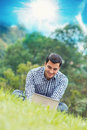 Happy young man with laptop outdoor outside Stock Image
