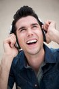 Happy young man listening to music on earphones outdoors portrait of a Stock Photos