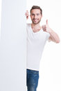 Happy young man look out from blank banner with thumb up isolated on white Royalty Free Stock Photos