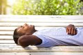 Happy young man lying on park bench with headphones Royalty Free Stock Photo