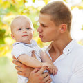 Happy young man men holding a smiling months old baby Stock Image