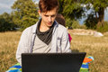 Happy young man in park writing article on his laptop Stock Image