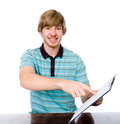 Happy young man points a finger at a blank sheet of sitting at t the table isolated on white background Royalty Free Stock Photo