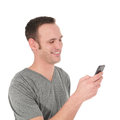 Happy young man reading a text message on his cell phone isolated on white Stock Photography