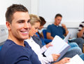 Happy young man sitting in class reading Stock Photos