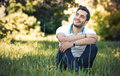 Happy young man sitting on meadow. Royalty Free Stock Photo