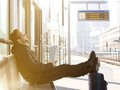 Happy young man sitting with travel bag at the train station Royalty Free Stock Photo