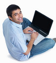 Happy young man sitting and working on laptop Royalty Free Stock Image
