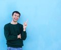 Happy young man smiling and pointing finger Royalty Free Stock Photo