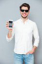 Happy young man in sunglasses holding blank screen cell phone Royalty Free Stock Photo