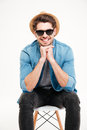 Happy young man in sunglasses sitting on chair and smiling Royalty Free Stock Photo