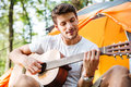 stock image of  Happy young man tourist sitting and playing guitar in forest