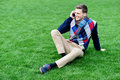 Happy young man using mobile phone on park casual talking a seated a grass Stock Photo