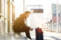 Happy young man waiting for train at station with bag Royalty Free Stock Photo