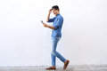 Happy young man walking on street looking at mobile phone Royalty Free Stock Photo