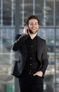 Happy young man walking and talking on mobile phone Royalty Free Stock Photo