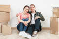 Happy young man and woman sitting near  cardboard boxes Royalty Free Stock Photo