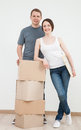 Happy young man and woman standing near cardboard boxes men women neutral background Royalty Free Stock Photo