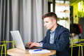 Happy young man works on his laptop to get all his business done early in the morning with his cup of coffee Royalty Free Stock Photo