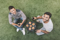 Happy young men sitting on grass with beer bottles and grilling meat Royalty Free Stock Photo