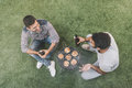 Happy young men sitting on grass with beer bottles and making barbecue Royalty Free Stock Photo