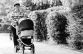 Happy young mother with baby in buggy walking Royalty Free Stock Photography