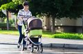 Happy young mother with baby in buggy walking Stock Photo