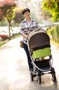 Happy young mother with baby in buggy walking Royalty Free Stock Photos