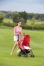 Happy young mother with baby in buggy walking a posing a stroller a park Stock Photos