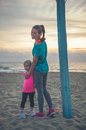 A happy young mother on the beach is standing with her daughter lovely at sundown she looking over shoulder smiling and lovingly Stock Image