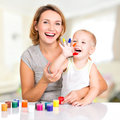 Happy young mother and child with painted hands indoors Stock Images