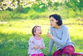 Happy young mother and her daughter blowing soap bubbles in park Stock Photos