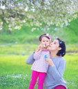Happy young mother and her daughter blowing soap bubbles in park Royalty Free Stock Image