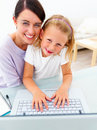 Happy young mother with her daughter using laptop Stock Images