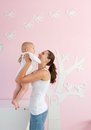Happy young mother lifting baby from crib at home portrait of a Royalty Free Stock Photography