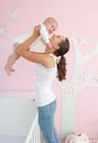 Happy young mother lifting cute baby out of crib portrait a in bedroom Stock Photo