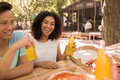 Happy young multiethnic friends students outdoors drinking juice eating pizza Royalty Free Stock Photo