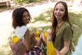 Happy young multiethnic friends students outdoors drinking juice Royalty Free Stock Photo