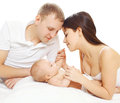 Happy young parents and baby lying on the bed together Stock Photo