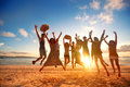 Happy young people jumping at the beach on beautiful sunset Royalty Free Stock Photo