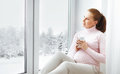 Happy young pregnant woman with  cup of tea on  window Royalty Free Stock Photo