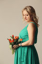 Happy young pregnant woman holding flowers with tulip in their hands Stock Photo