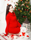 Happy young pregnant woman near the christmas tree sitting Stock Image