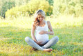 Happy young pregnant woman sitting on grass doing yoga in summer