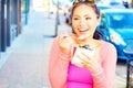 Happy young pretty mixed race female eating frozen yogurt while looking away horizontal shot Stock Photography