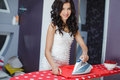 Happy young pretty woman ironing services on the house beautiful facilities in room with iron looking Stock Image