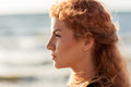 Happy young redhead woman face on beach Royalty Free Stock Photo