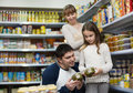 Happy young smiling parents with little girl buying tinned food at grocery Stock Photography
